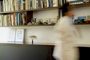 本棚の前を歩く男性の写真素材 [FYI03353358]