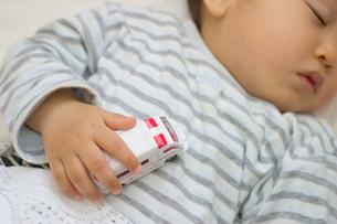 おもちゃをつかんで眠る日本人の男の子の赤ちゃんの写真素材 [FYI03353507]