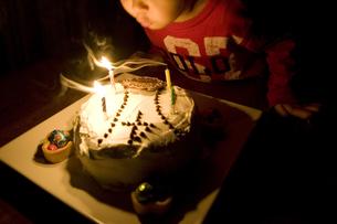 ケーキのろうそくを吹き消す男の子の写真素材 [FYI03353526]