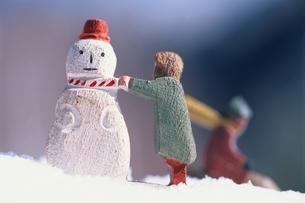 雪だるまをつくる女の子とそりをする男の子の2個の木彫りの人形の写真素材 [FYI03353624]