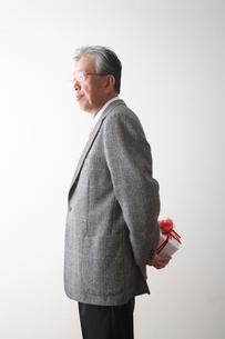 プレゼントを持つシニア男性の写真素材 [FYI03354194]