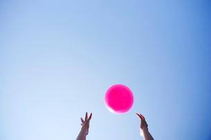 ピンクのボールを受け取ろうとする手の写真素材 [FYI03354751]