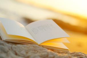 夕陽指す海辺に置かれた本の写真素材 [FYI03354825]