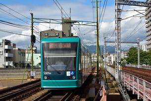 鉄橋を渡る広島電鉄低床車の写真素材 [FYI03355924]