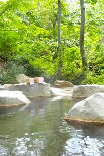 手ぬぐいをかけた桶をおいた露天風呂の写真素材 [FYI03356147]