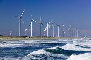 風車と海と工業地帯の煙突の写真素材 [FYI03356357]