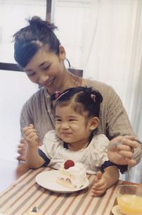 女の子を膝に乗せてショートケーキを食べさせる母親 日本人の写真素材 [FYI03357629]