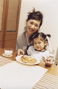 お母さんの膝の上に乗りホットケーキを食べる女の子の写真素材 [FYI03357633]