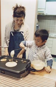 ホットケーキを焼く男の子とエプロン姿のお母さんの写真素材 [FYI03357636]