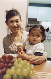 お母さんの膝の上に乗りリンゴを食べる女の子の写真素材 [FYI03357639]