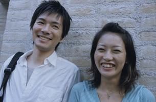 レンガの壁に寄り掛かる日本人カップルの写真素材 [FYI03357648]