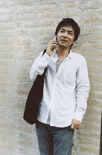 レンガの壁に寄り掛かり携帯電話で話す日本人男性の写真素材 [FYI03357666]
