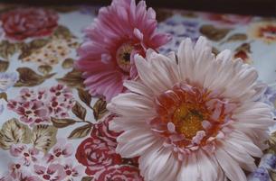 花柄のテーブルクロスとピンク色の造花の写真素材 [FYI03357669]