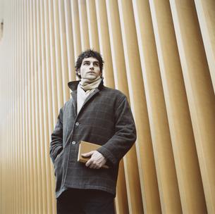 本を抱えコートを着た外国人男性 冬の写真素材 [FYI03358289]