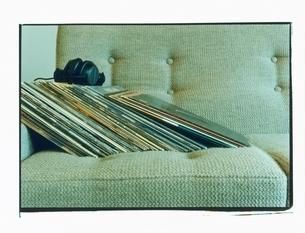 部屋のソファに置かれた複数のレコードとヘッドフォンの写真素材 [FYI03358353]