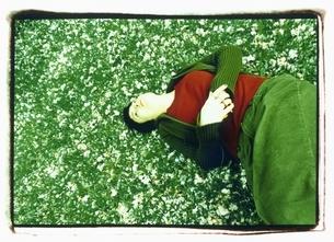 桜の花びらに寝転がる外国人女性の写真素材 [FYI03358354]