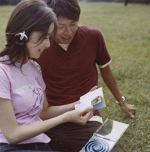芝生でCDジャケットを見る日本人カップルの写真素材 [FYI03358356]