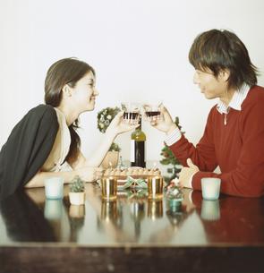 ワインで乾杯をする日本人カップルとクリスマスケーキの写真素材 [FYI03358375]