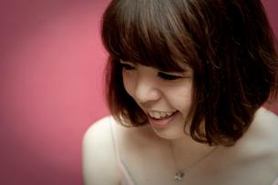 うつむいて笑うボブヘアの20代女性の写真素材 [FYI03358379]