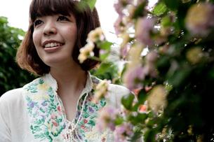 路地裏で花を眺めるボブヘアの20代女性の写真素材 [FYI03358386]