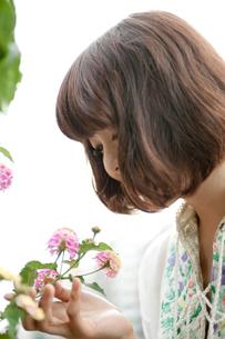 ピンクと黄色の花を触るボブヘアの20代女性の写真素材 [FYI03358388]