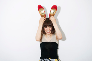 赤い靴を頭に乗せてバニーガールの真似をする20代女性の写真素材 [FYI03358390]