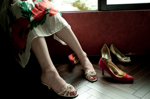 窓辺に座るサンダルを履いた女性の足元とヒール靴の写真素材 [FYI03358391]