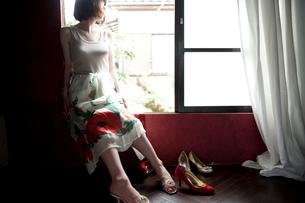 窓辺に座ったスカートをはいている女性とヒール靴の写真素材 [FYI03358393]
