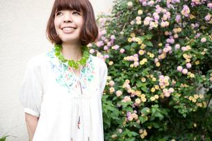 ピンクと黄色の花の横で笑うボブヘアの20代女性の写真素材 [FYI03358395]