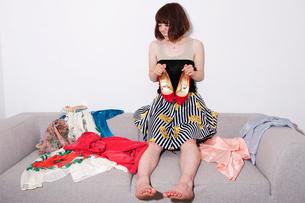 服の広がったソファに座ってヒール靴を持つ20代女性の写真素材 [FYI03358398]