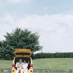 自動車のトランクに腰掛ける日本人中高年夫婦の写真素材 [FYI03358488]