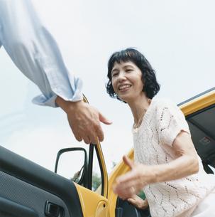 助手席から外に出る日本人中高年女性とエスコートする男性の手の写真素材 [FYI03358490]