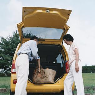 自動車のトランクから荷物を運ぶ日本人中高年夫婦の写真素材 [FYI03358491]