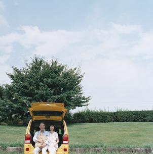 自動車のトランクに腰掛ける日本人中高年夫婦の写真素材 [FYI03358492]