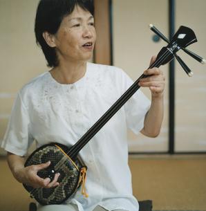和室で三味線を演奏する日本人中高年女性の写真素材 [FYI03358495]