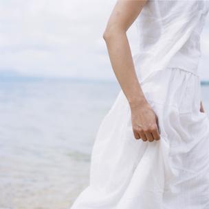 海辺に立つ白い洋服の女性の写真素材 [FYI03358498]