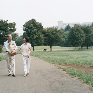 買い物袋を抱え公園を歩く日本人中高年夫婦の写真素材 [FYI03358499]