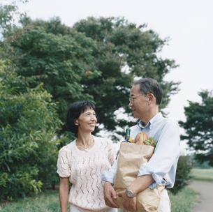 買い物袋を抱え公園を歩く日本人中高年夫婦の写真素材 [FYI03358502]