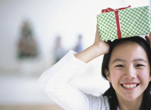 ギフトボックスを頭に乗せた日本人の女の子の写真素材 [FYI03359604]