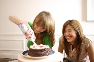ケーキのデコレーションをする2人の女性の写真素材 [FYI03360270]