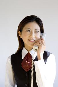 電話をかける日本人ビジネスウーマンの写真素材 [FYI03361436]