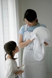 台所で皿を拭いている親子の写真素材 [FYI03361561]