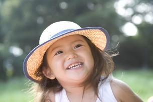 麦わら帽子をかぶっている女の子の写真素材 [FYI03361576]