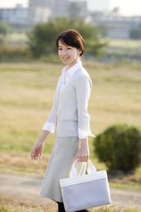 鞄を持って歩く女性の写真素材 [FYI03361620]