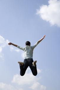 青空へジャンプする女性の後姿の写真素材 [FYI03361672]