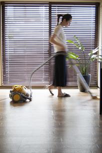 リビングで掃除機をかける女性の写真素材 [FYI03361837]