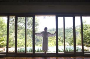 窓を開けるバスローブ姿の女性の写真素材 [FYI03361908]