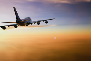 夕日に向かって飛ぶ飛行機の模型の写真素材 [FYI03361919]