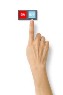 スイッチのオフを押そうとする右手の写真素材 [FYI03361949]