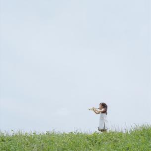 おもちゃのラッパを外で吹く女の子の写真素材 [FYI03362312]